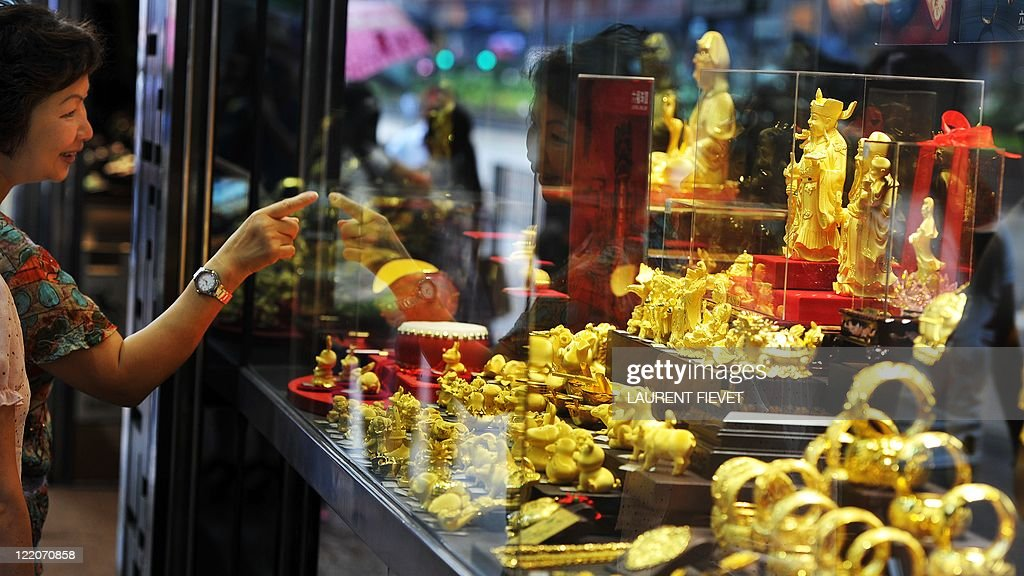 A woman points to gold ornaments inside : News Photo