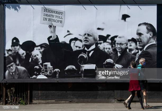 A woman points towards a satirical poster from the group Led By Donkeys depicting Boris Johnson as former British prime minister Neville Chamberlain...