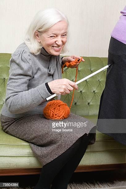 femme toucher du bout des doigts ami avec une aiguille à tricoter - vieilles fesses photos et images de collection