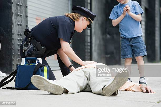 woman police officer administering first aid to a senior man - kids first aid kit stock pictures, royalty-free photos & images
