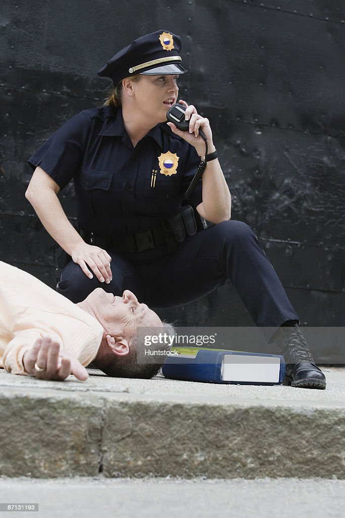 Woman police officer asking for assistance on the hand mike : Stock Photo