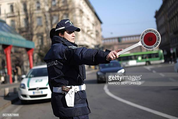 A woman police officer controls traffic in Milan on December 28 2015 Drivers in Milan will face a limit on daytime travel three days as the northern...