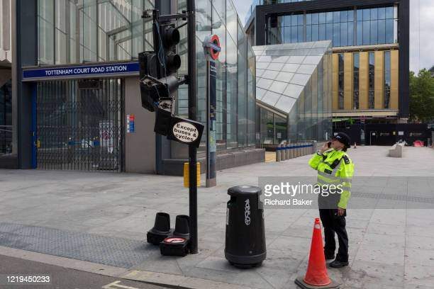 A woman police officer reports by radio the damage to a smashed traffic and pedestrian light that has been hit by a doubledecker London bus and...