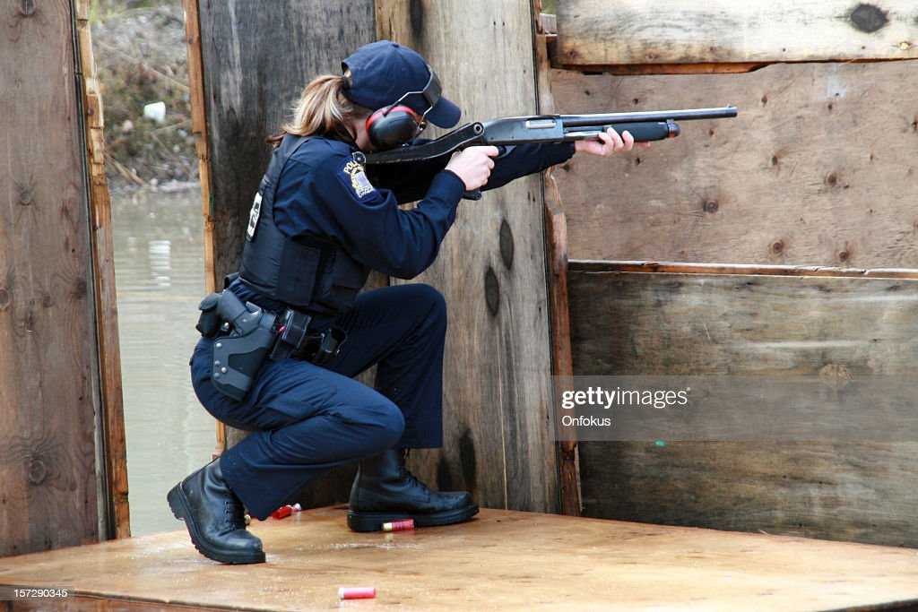 Woman Police Officer Shooting Shotgun at the Practice Field : Stock Photo