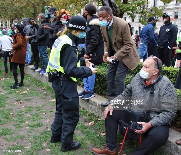 Woman police officer wearing a mask speaks to a press photographer before the start of the protest. With a number of expected demonstrations taking...