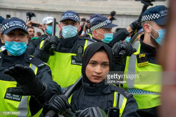 Woman Police officer without a face mask, holding a baton during the demonstration. Police and demonstrators clash at the We Do Not Consent protests...