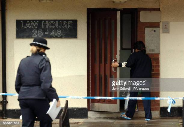 A woman police officer wtches a resident enter Law House on Maybury Road Barking which Essex police have cordoned off this morning following the...