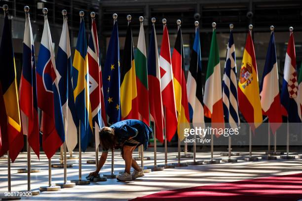 A woman polishes a flag pole at the Council of the European Union on the first day of the European Council leaders' summit on June 28 2018 in...