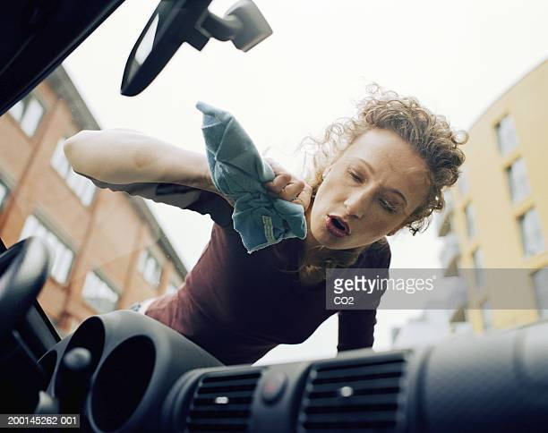 Woman polishing car windscreen, low angle view
