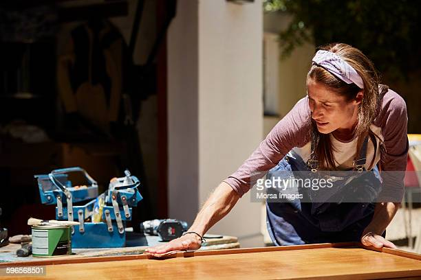Woman polishing furniture outdoors