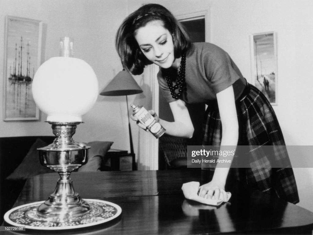 Woman polishing the living room table, 28 May 1963. : News Photo