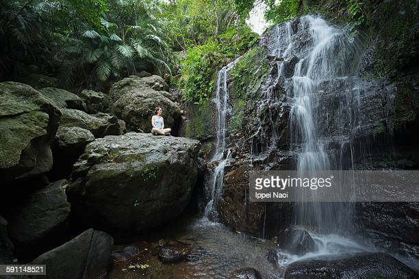 Woman pondering at waterfall in jungle, Okinawa