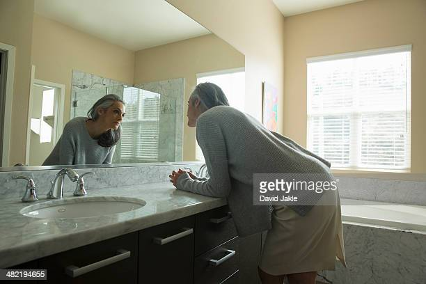 woman pondering in front of mirror - older woman bending over stock pictures, royalty-free photos & images