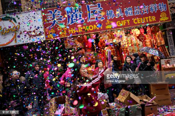 A woman pops confetti during a cultural festival to mark the first day of the Lunar New Year in Chinatown neighborhood in Manhattan February 16 2018...