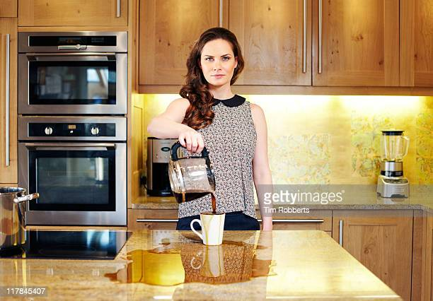Woman poring coffee into cup and over work-surface