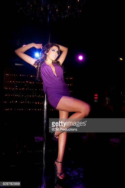 Woman portrait holding a pole in club