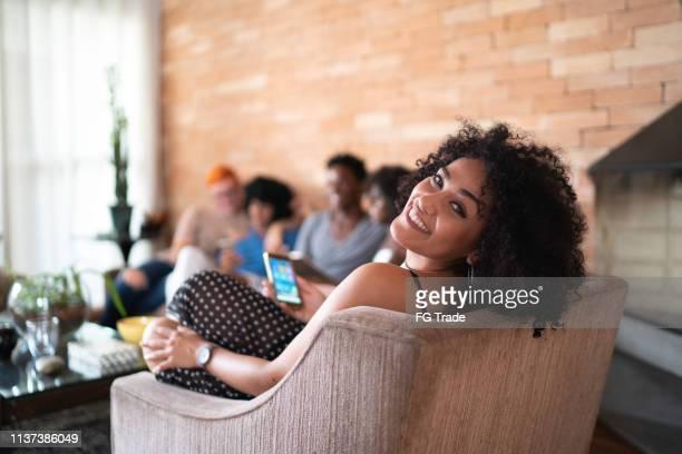 vrouw portret met behulp van mobile op social gathering thuis - mobile stockfoto's en -beelden