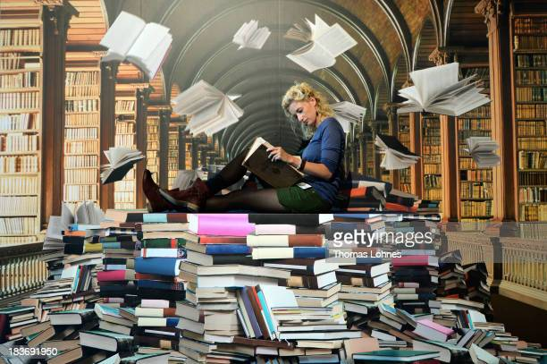 A woman pose for a photo in front of photowall with motiv of a phantasy library at the 2013 Frankfurt Book Fair on October 9 2013 in Frankfurt...