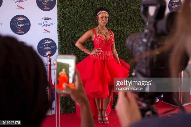 A woman poses as she arrives to attend the Met horse race at Kenilworth race track on January 27 in Cape Town The Met is one of South Africa's...