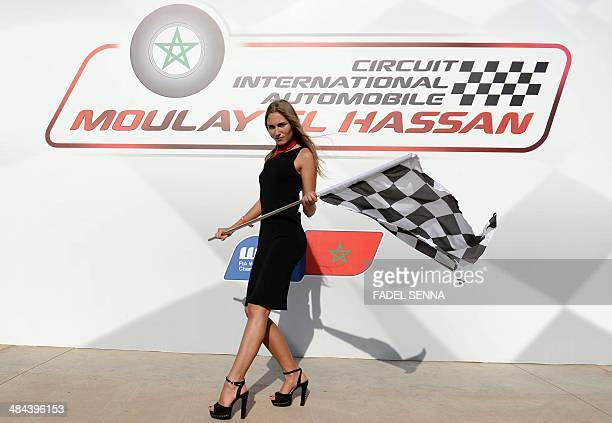 Woman poses as she waves the checkered flag during the qualifying opening round of the FIA World Touring Car Championship on April 12, 2014 at the...