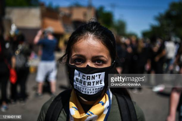 "Woman poses as she wears a mask saying ""I can't breathe"" at the makeshift memorial in honour of George Floyd, who died while in custody of the..."