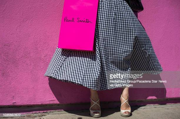 A woman poses at Paul Smith's flagship store on Melrose Avenue in Los Angeles as painters finish covering up graffiti that read Go F Ur Selfie on the...