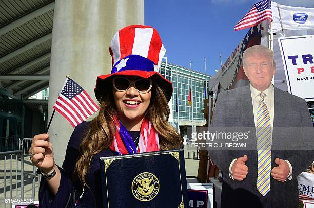 A woman poses beside a cardboard cutout of Donald Trump with her certificate of naturalization as volunteers and supporters of Republican...