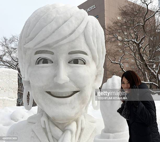 A woman poses beside the large snow sculpture entitled Winter OMoTeNaShi or winter hospitality which came from Japan's Tokyo Olympic bid committee...