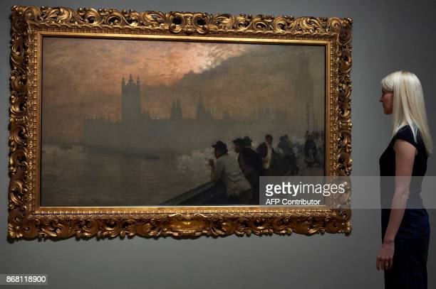 A woman poses by a painting titled Westminster by French based Italian artist Giuseppe de Nittis during a press preview for the exhibition French...