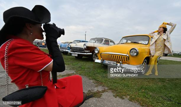 Woman poses by a retro car, an exhibit of OldCarLand festival, at the open-air State Aviation Museum in Kiev during the festival's opening on...