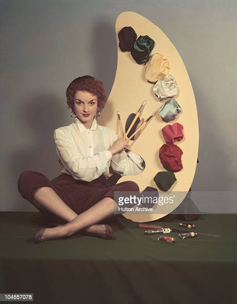A woman poses crosslegged with three paint brushes next to a large paint palette circa 1955