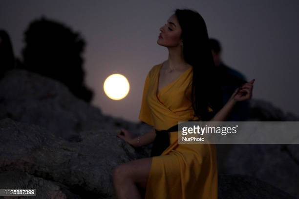 A woman poses during the Super Moon rises in Athens Greece on February 19 2019 A full moon rises in the night sky known as a Snow Moon and the...