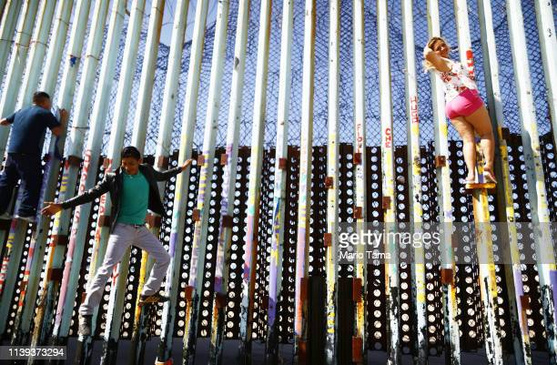 A woman poses for a photo as a man jumps back down from the border barrier on the USMexico barrier on the beach on March 30 2019 in Tijuana Mexico...