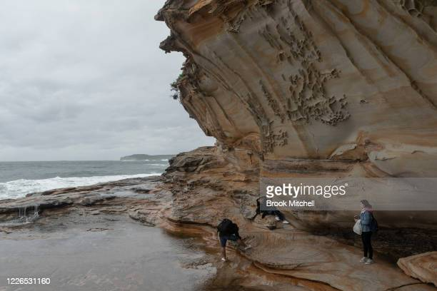 A woman poses for a photo as large waves hit the coast at La Perouse on May 23 2020 in Sydney Australia Winter weather including rain and strong...
