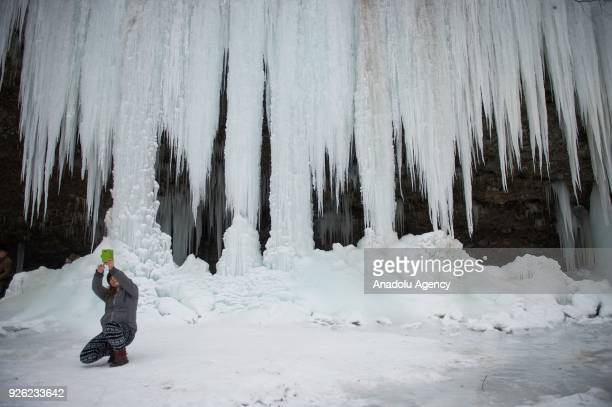 A woman poses for a photo in front of the icefall Siklava Skala in Spisska Nova Ves district Slovakia on March 02 2018 The icefall Siklava Skala with...