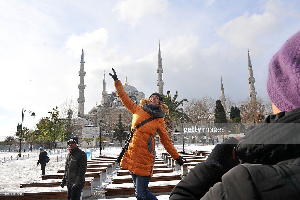 A woman poses for a photo in the snow covered Sultanahmet square in Istanbul on January 8, 2013. Heavy snowfall blanketed Turkey's commercial hub Istanbul, a city of 15 million, paralysing daily life, disrupting air traffic and land transport. Officials said the snow is expected to continue until late tomorrow, according to the weather forecast.