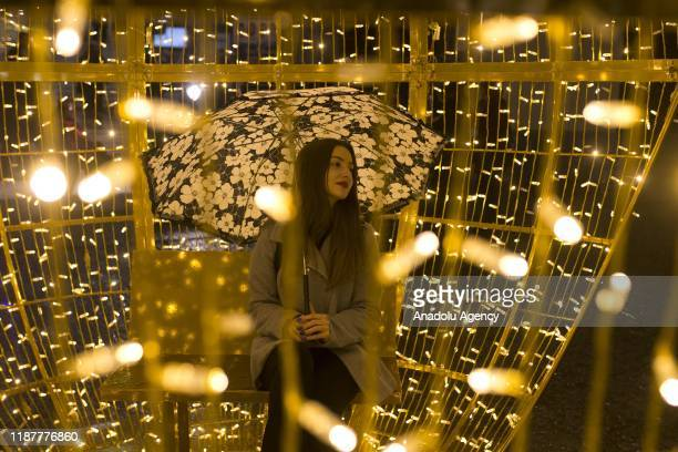 A woman poses for a photo inside an illuminated decoration within the Christmas preparations at Syntagma Square on December 10 2019 in Athens Greece