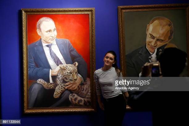 A woman poses for a photo near paintings depicting Russian President Vladimir Putin at the 'SUPERPUTIN' exhibition at UMAM Museum in Moscow Russia on...