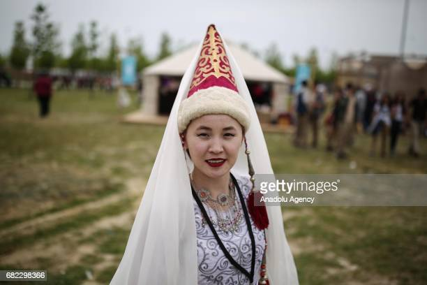 Woman poses for a photo near the traditional Kyrgyz tent on the bridal veil ceremony according to the Kyrgyz wedding customs during Ethnosports...