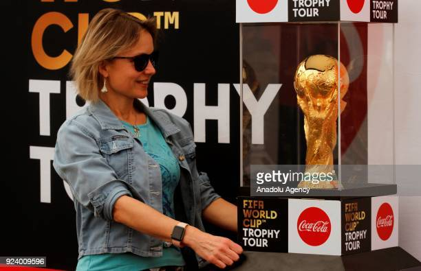 A woman poses for a photo near the World Cup Trophy at Hilton Hotel after the trophy was brought to Ethiopia within the 2018 FIFA World Cup Trophy...