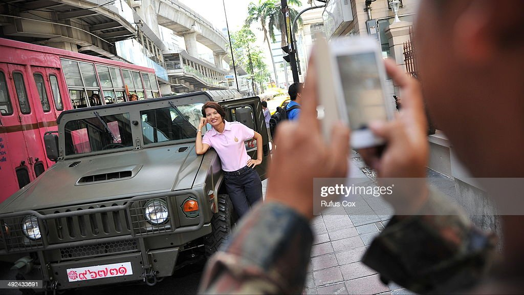 A woman poses for a photo next to a Thai Army vehicle after martial law was declared on May 20, 2014 in Bangkok, Thailand. The army imposed martial law across Thailand amid a deepening political crisis that has seen six months of protests and claimed at least 28 lives.