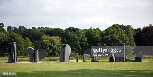 A woman poses for a photograph alongside a sculpture entitled 'Promenade' by artist Sir Anthony Caro as it stands on display as part of the...