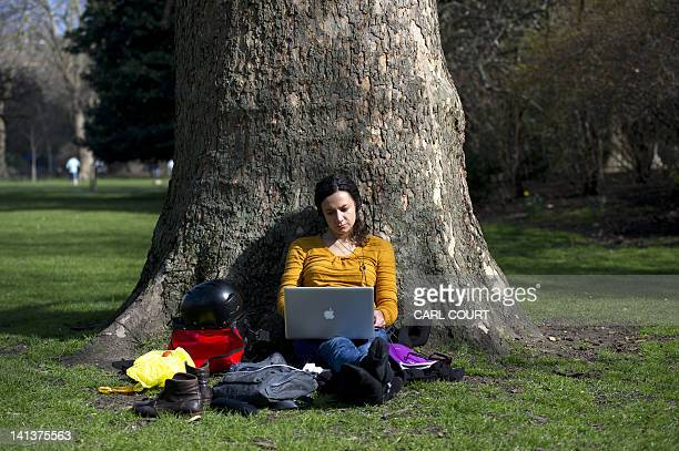 A woman poses for a photograph as she works on her laptop sitting at the base of a tree on the grass enjoying the warm weather in a park in central...