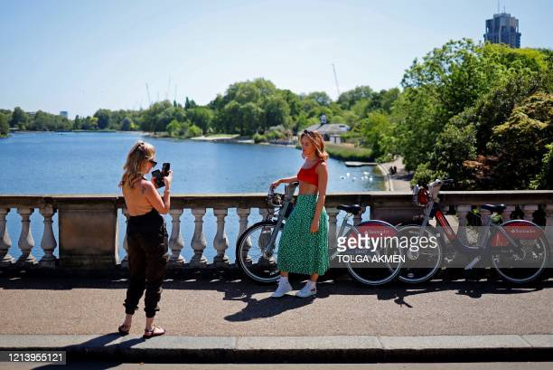 A woman poses for a photograph as they enjoy the afternoon sunshine in Hyde Park London on May 19 following the relaxing of lockdown restrictions...