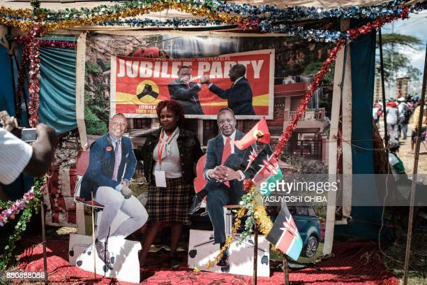 A woman poses for a photograph between posters of Kenya's President Uhuru Kenyatta and VicePresident William Ruto at a temporary installed photo...