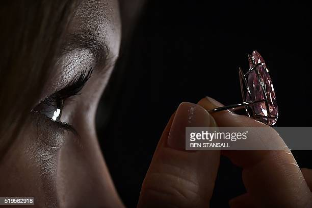 A woman poses for a photograph holding a vivid pink pearshaped 1538 carat diamond known as the 'Unique Pink' during a press preview at Sotheby's...