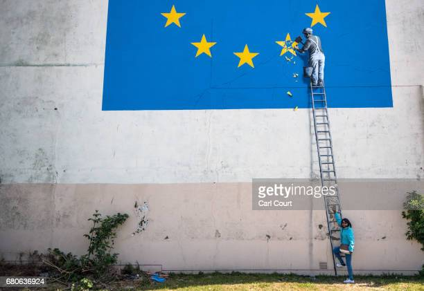 A woman poses for a photograph next to a recently painted mural by British graffiti artist Banksy depicting a workman chipping away at one of the...