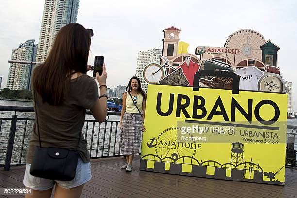 A woman poses for a photograph next to an advertisement at Asiatique The Riverfront openair mall in Bangkok Thailand on Friday Dec 18 2015 Thai...