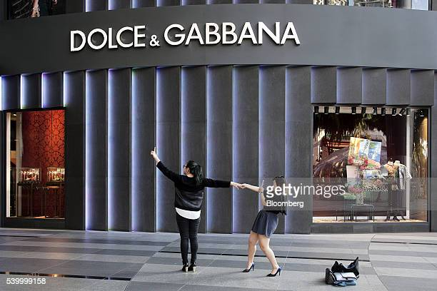 A woman poses for a photograph outside a a Dolce Gabbana Srl boutique luxury store at the Ion Orchard shopping mall on Orchard Road in Singapore on...