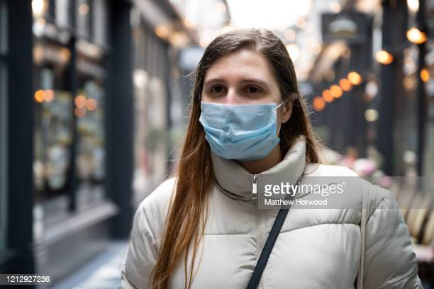 A woman poses for a photograph wearing a surgical mask in Castle Arcade on March 17 2020 in Cardiff Wales Boris Johnson held the first of his public...